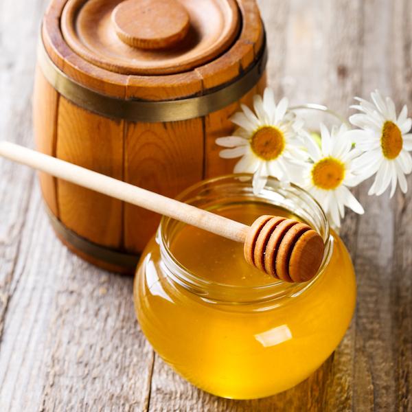 Üvegben méz, rajta mézkanál, mellette kamilla és egy kis fahordó.