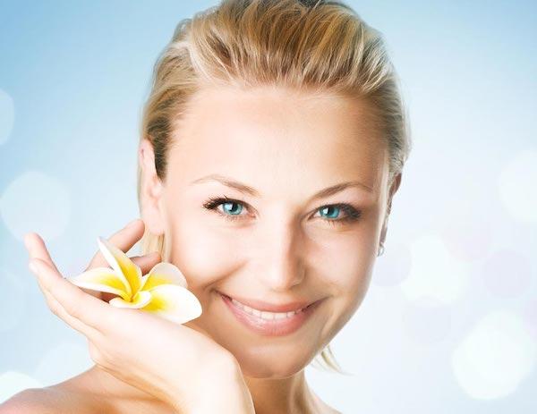 50-es, fiatalos nő mosolyog a kamerába, kezében egy virágot tartva.