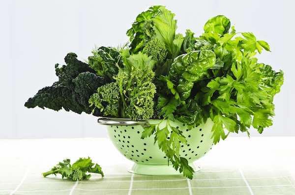 Különféle zöld leveles zöldségek egy szűrőben.
