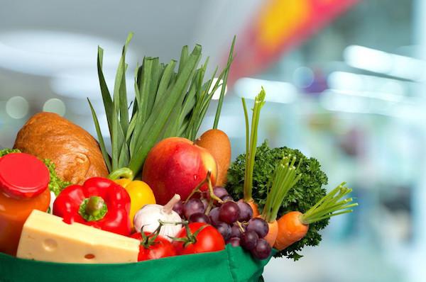 Különféle zöldségek és gyümölcsök egy zöld bevásárlószatyorban.