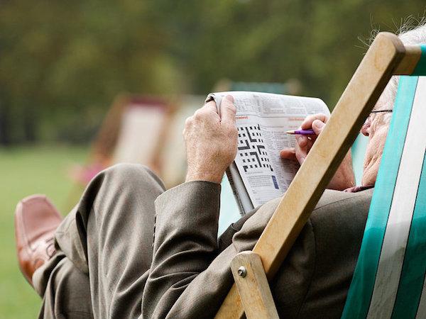 Idős úr keresztrejtvényt fejt pihenőszékében kinn, a zöldben.