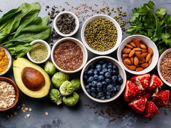 Egészséges táplálékok egymás mellett: gránátalma, áfonya, mandula, avokádó, hüvelyesek, kelbimbó, spenót, zabpehely.
