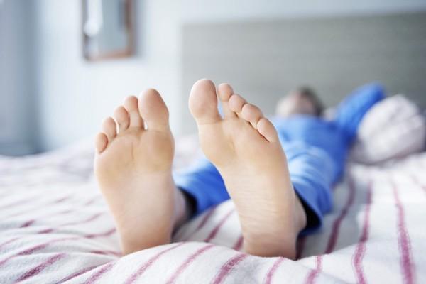 Pizsamában fekvő férfi a lába felől fotózva.