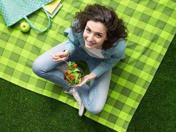 Fiatal tini zöld kockás pikniktakarón ülve salátá eszik, mellette egy zöldalma.