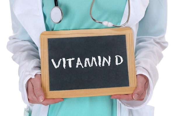 Orvosi köpenyben, fonendoszkóppal a nyakában egy D-vitamin feliratú táblát tart kezében egy hölgy.