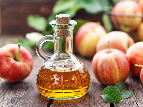 Almaecet díszes üvegben, mellette almák.