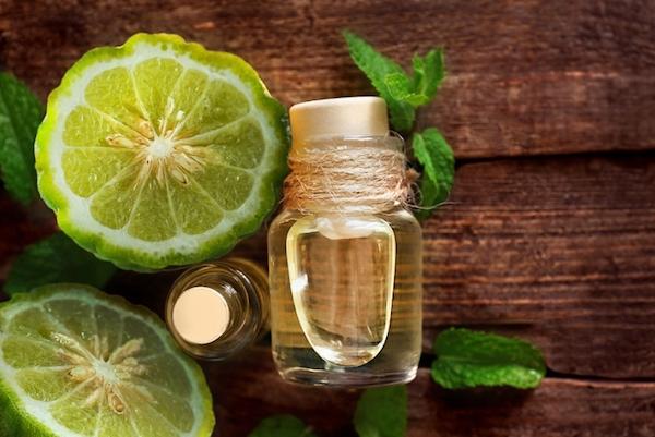 A lime-hoz hasonló bergamott kettévágva, mellette kis üvegben a belőle készült illóolaj kis üvegcsében.