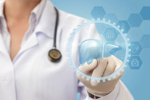 Doktornő mutat gumikesztyűs kezével egy érintőképernyőre, amely májat ábrázol.