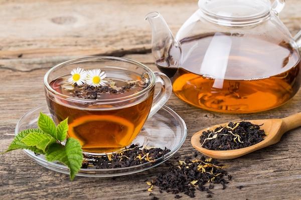 Fekete tea üvegkancsóban és üvegpohárban.