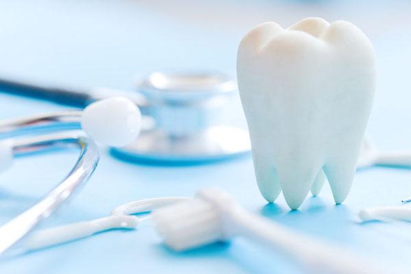 Fogászati tükör, nyelvtisztító, fogselyem és egy fehér műanyagból készült fog egymás mellett – a fogászati prevenció eszközei.