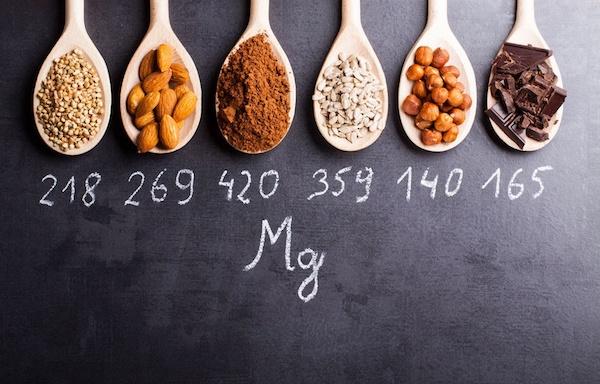 Magnéziumban gazdag élelmiszerek fakanalakban, mindegyik alatt krétával megjelölve a magnéziumtartalmát.