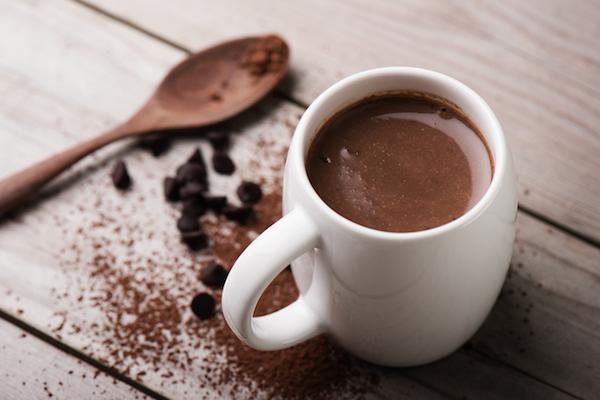Egy csésze forró kakaó, mellette fakanál, kakaószórás.