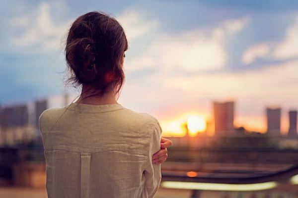 Nő vállait átfogva nézi a házak között lebukó nap sugarait.