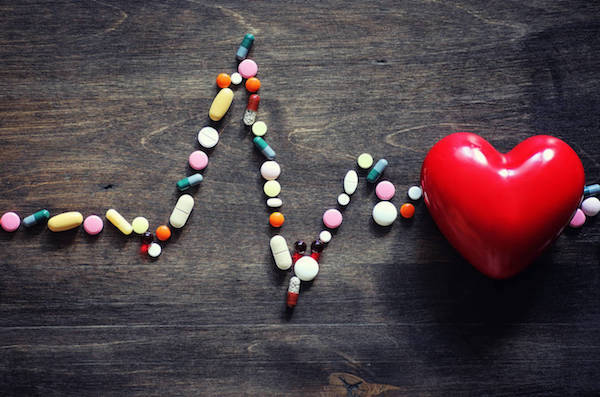Piros műanyag szív, mellette EKG-görbeként kirakott különféle színű és formájú étrend-kiegészítők.