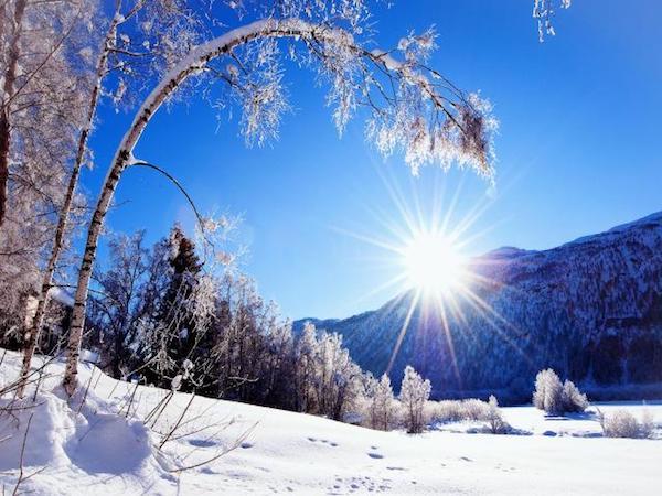 Téli, havas tájra rásüt a nap fénye egy hegy mögül.