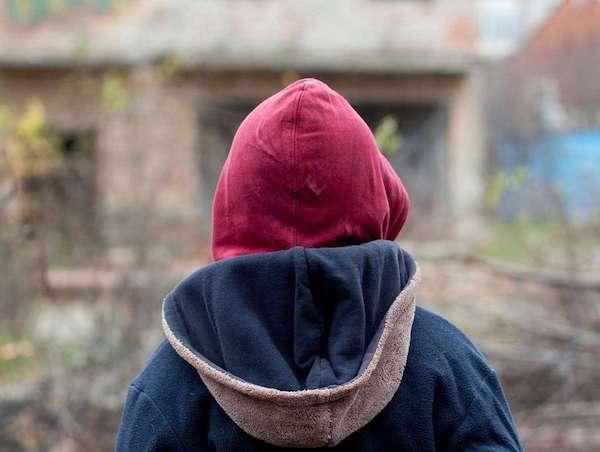 Csuklyás pulóvert viselő fiú egy romos, elhanyagolt környezetben.