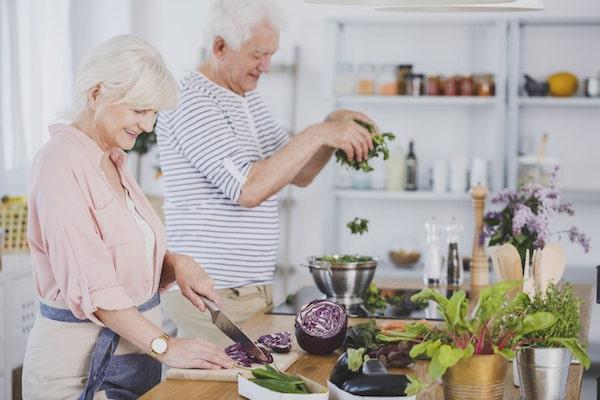 Idősebb házaspár együtt készíti a vacsorát konyhájukban.