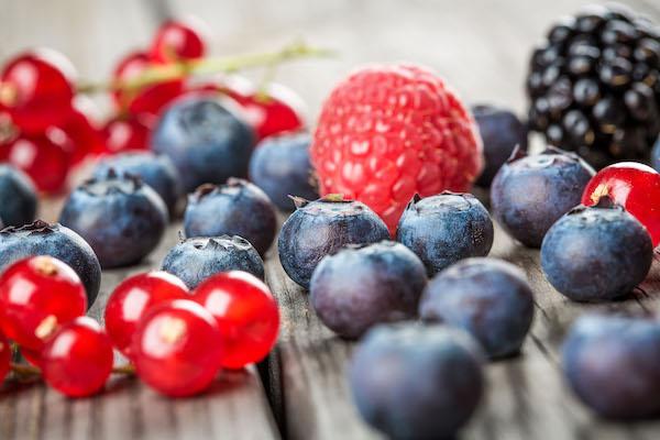 Különféle bogyós gyümölcsök egymás mellett egy faasztalon.