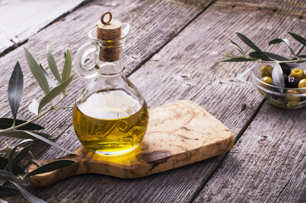 Extraszűz olívaolaj díszes üvegben, mellette olívabogyók.