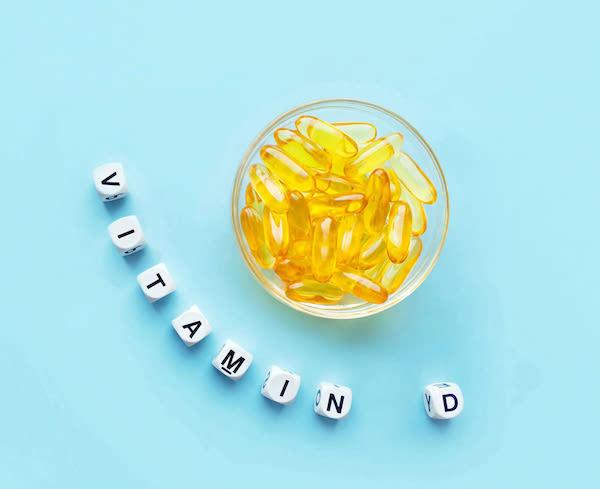 D-vitaminok üvegtálban, mellette kirakva a vitamin betűi.