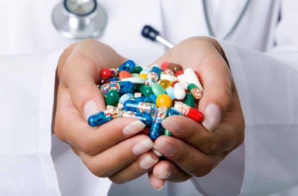 Egy doktornő keze tele színes gyógyszerekkel, kapszulákkal.