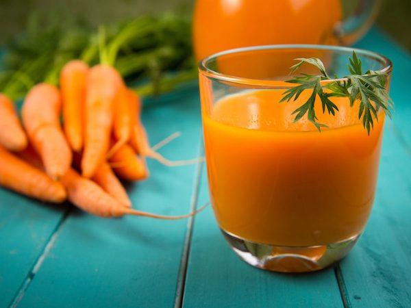 Egy pohár frissen facsart sárgarépalé, mellette a egy csokor répa.
