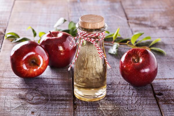 Almaecet kis üvegben, mellette három piros alma.