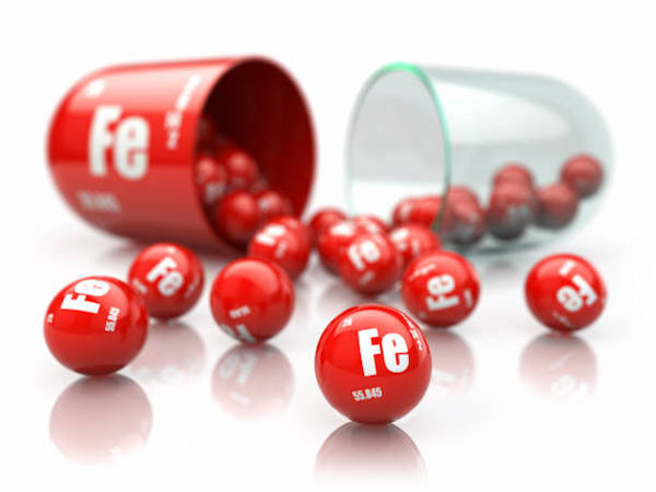 A vas kémiai vegyjelével ellátott piros golyók kiöntve egy piros + üveg kapszulából.