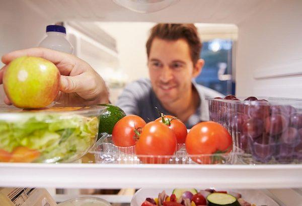 Egy férfi benyúl a hűtőszekrénybe, kiemel onnét egy almát.