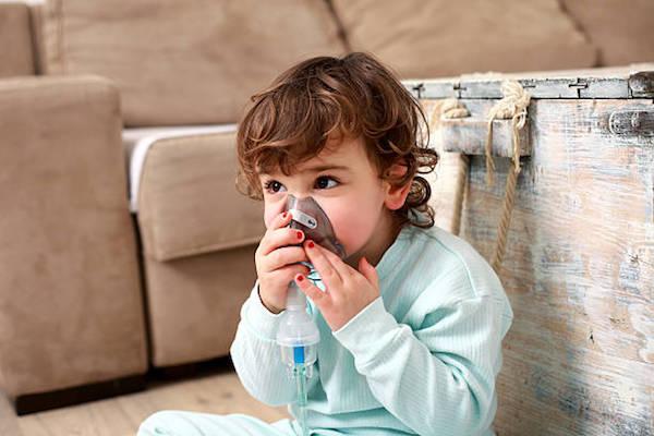 Kisgyermek asztmapipát szorít az orrához.