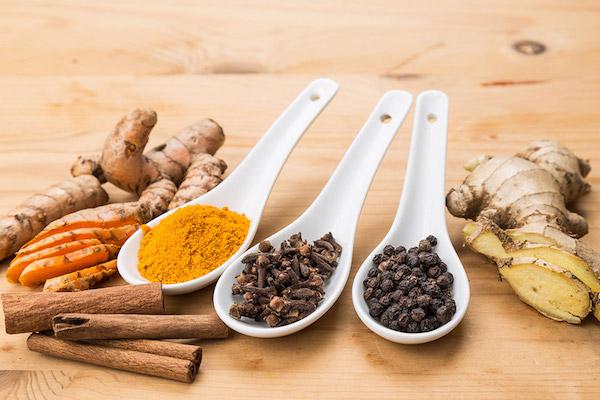 5 különböző indiai fűszer egymás mellett: kurkuma, szegfűszeg, fahéj, fekete bors és gyömbér.