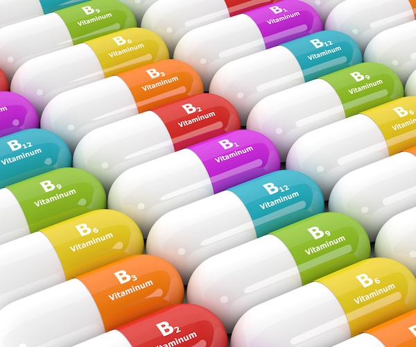 Különféle B-vitaminok színes kapszulákban egymás mellett.