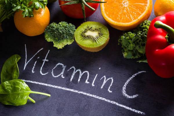 C-vitamint tartalmazó gyümölcsök és vitaminok egy fekete táblán.