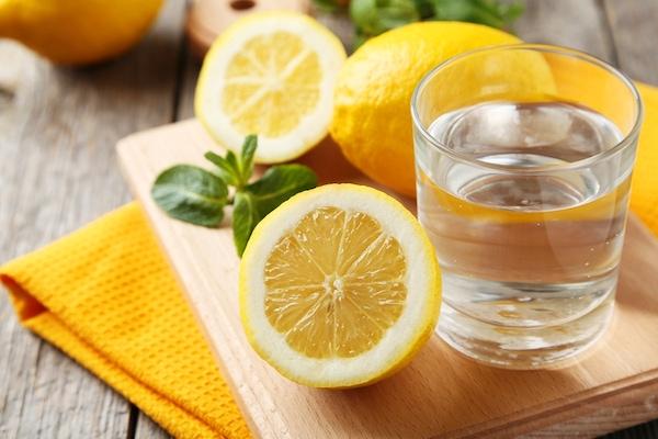 Pohár víz, mellette citromok.