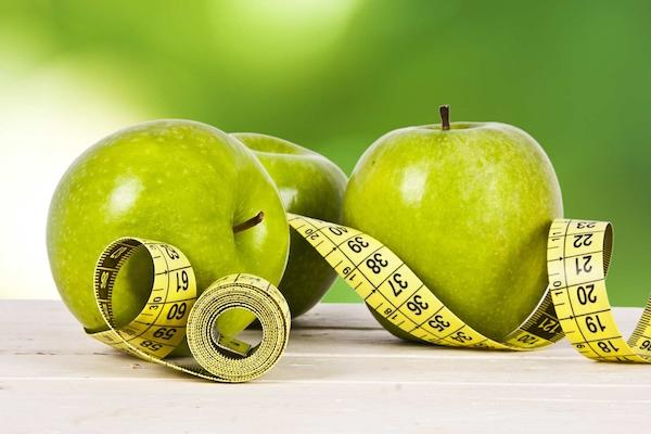 Három zöld alma egymás mellett, közöttük centiméter, ami a fogyókúrára utal.