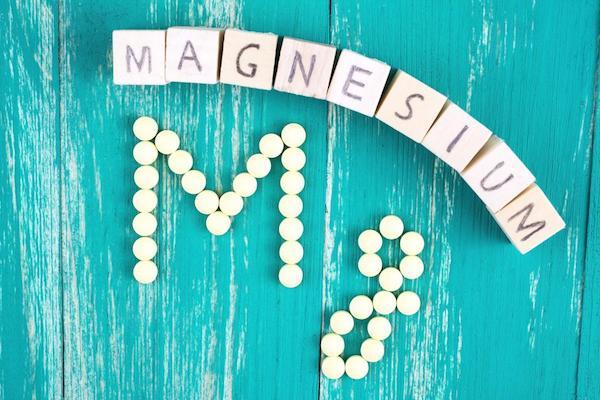 Türkiz asztalon a magnézium betűi és vegyjele kirakva.