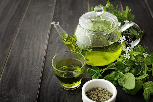 Szemes zöld tea és a belőle készült ital üvegkancsóban.