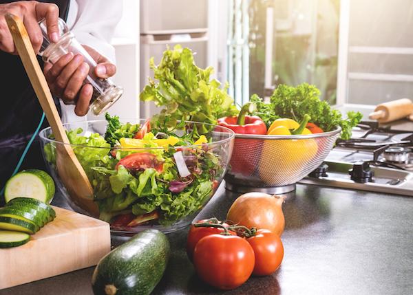 Zöldségsaláta ízesítése fűszermalomból.