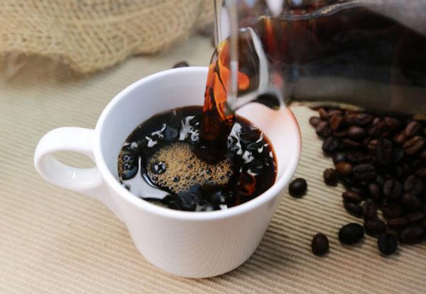 Üveg kiöntőből kávét töltenek egy kisebb csészébe.