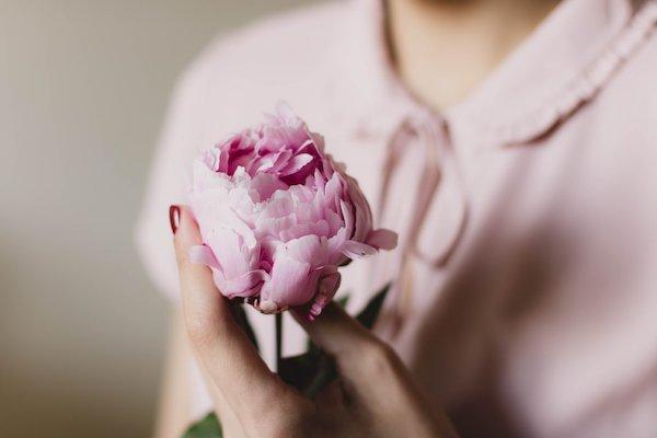 Rózsaszín blúzban lévő hölgy egy bazsarózsát tart a kezében.
