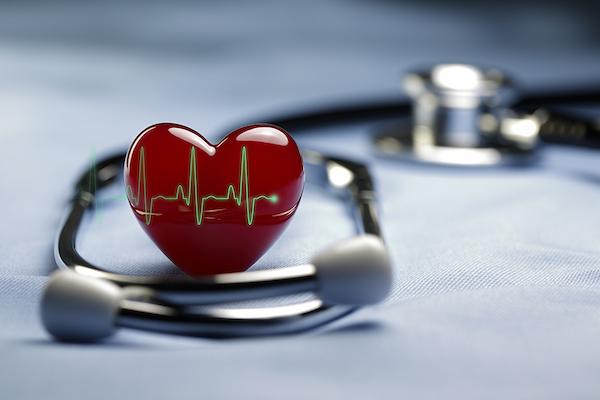 Fonendoszkóp mellett piros szív EKG-görbével.