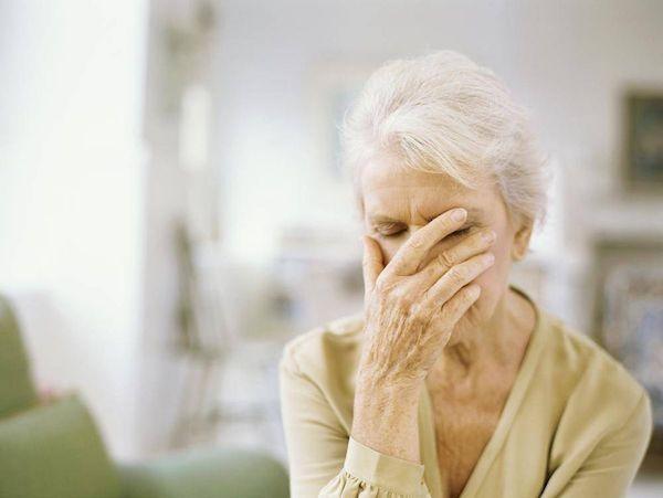 Alzheimer-kórban szenvedő idős hölgy, keze az arca előtt.