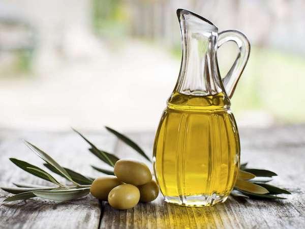 Olívabogyók, mellette egy kis üvegkancsóban olívaolaj.