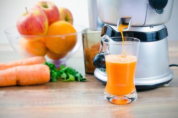 Gyümölcscentrifugából kifolyó gyümölcslé, mellette sárgarépa, narancs és alma.