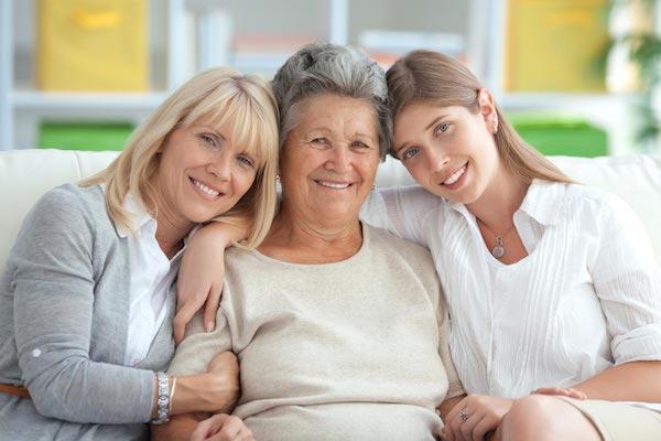 Három generáció egymás mellett a kanapén ülve mosolyog bele a kamerába.