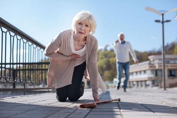 Idős hölgynek valószínűleg szívrohama van, elesik, kezét a mellkaásra szorítja, férje kiált utána.