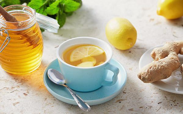 Gyömbértea kék csészében, mellette méz, gyömbér és citrom.