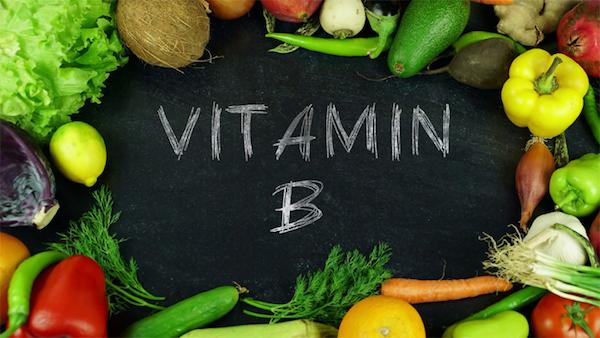 Különféle zöldségek és gyümölcsök fekete alapon, mellyel krétával a B-vitamin szót írták.