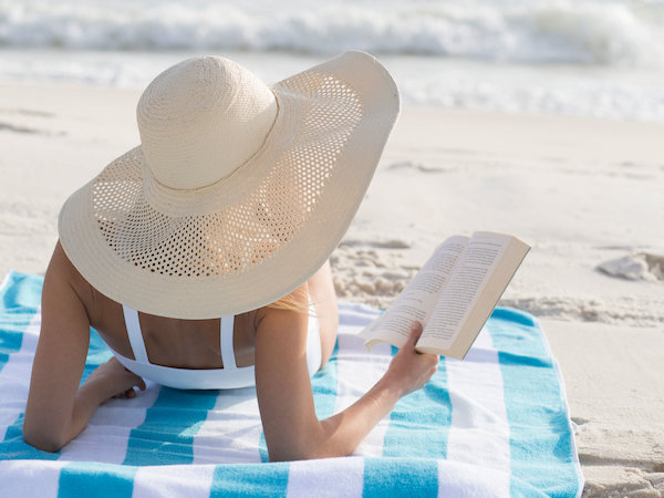Tengerparti homokban szalmakalapban könyvet olvas egy nő.