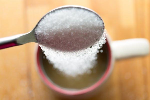 Egy pohár folyadékba kiskanállal cukrot szórnak.